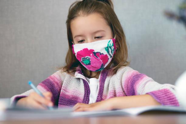 Schulmädchen Mädchen in Maske studieren Hausaufgaben zu Hause, soziale Distanz während Quarantäne Coronavirus – Foto