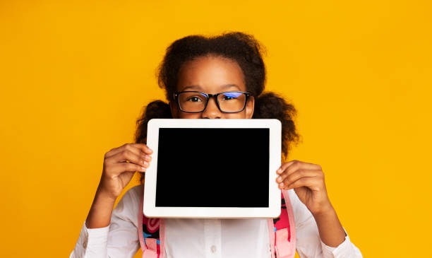 Schoolgirl Holding Digital Tablet With Blank Screen On Yellow Background stock photo