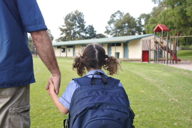 Schoolgirl holding her fathers hand on the way to school stock photo