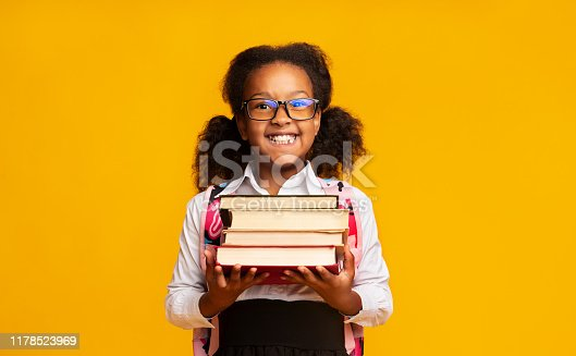 istock Schoolgirl Holding Stack Of Books Smiling At Camera, Studio Shot 1178523969