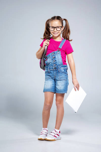Schoolgirl in glasses with backpack and textbook on the gray background stock photo