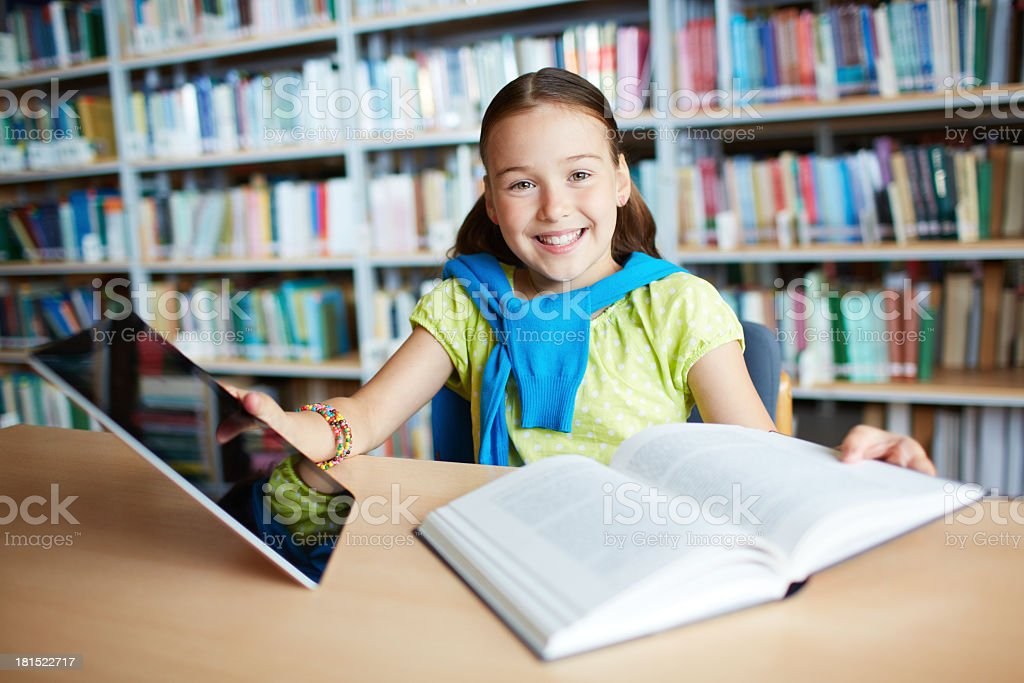 Schoolgirl in library with book and tablet royalty-free stock photo