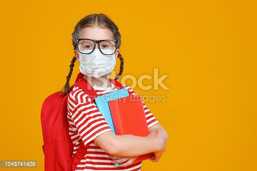 istock Schoolgirl in mask studying during quarantine 1243741425