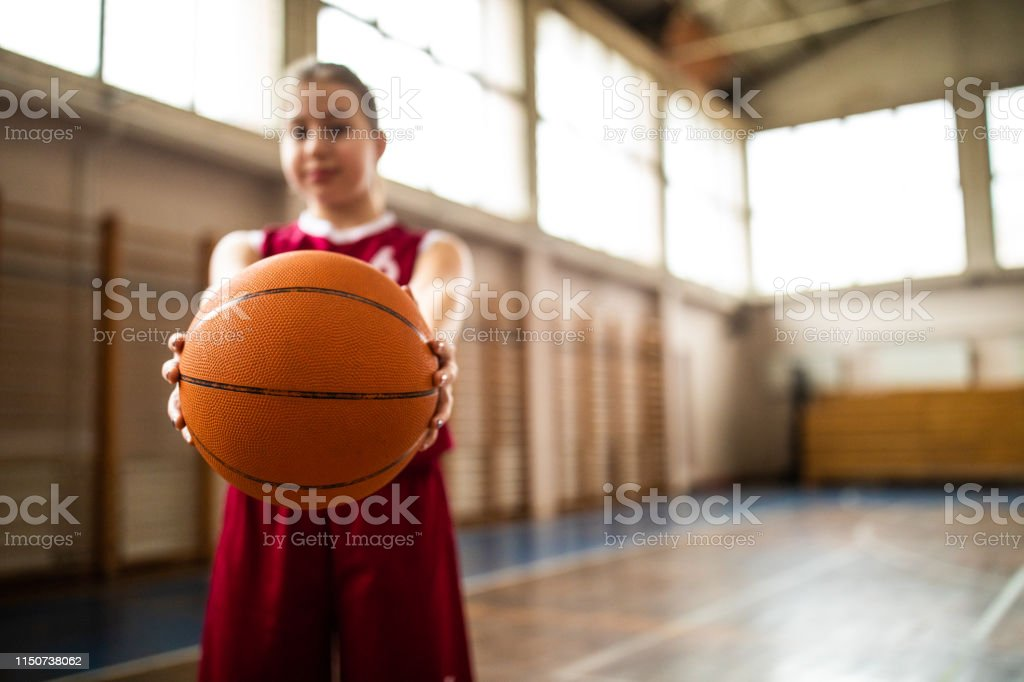 Cute female basketball player standing in school gym and smiling,...
