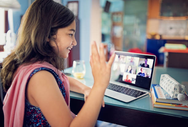 Schoolgirl is e-learning and video conferencing at home stock photo