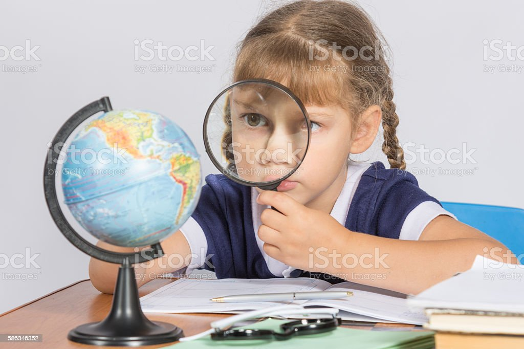 Schoolgirl looking at globe through a magnifying glass stock photo