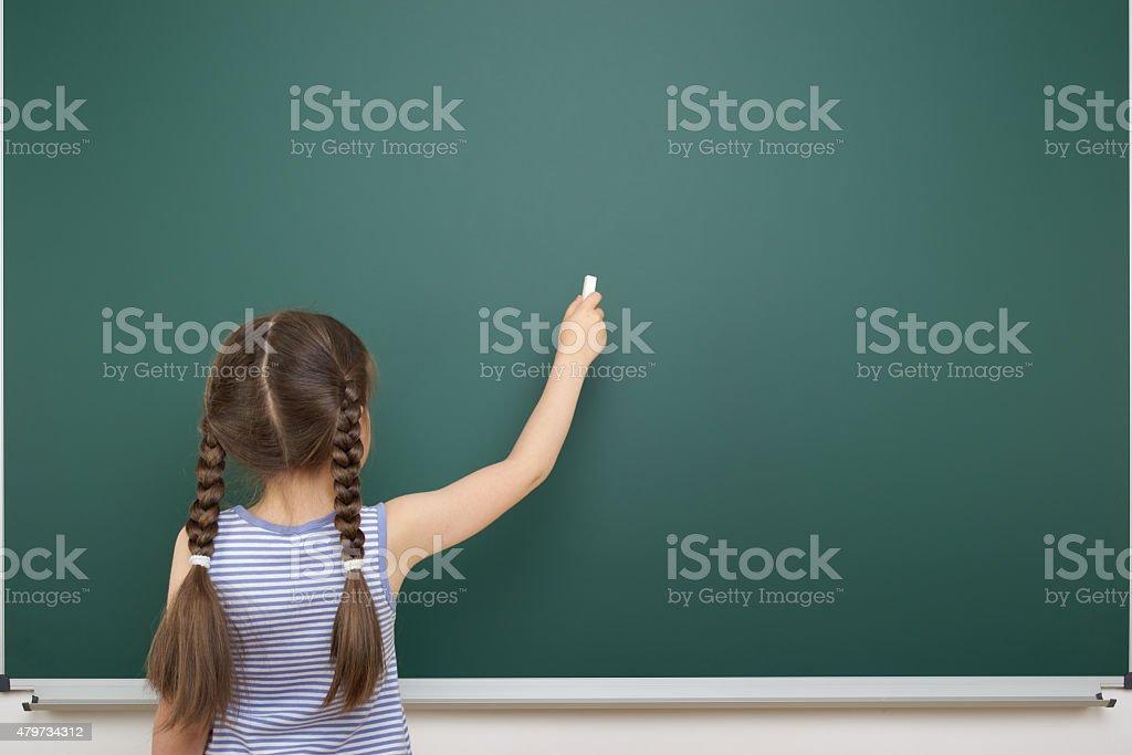 Schoolgirl near school board stock photo