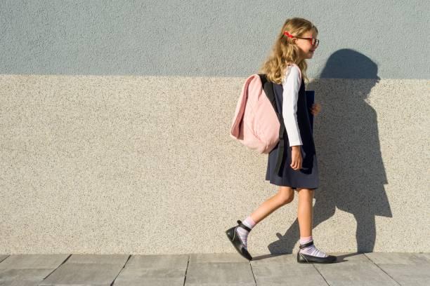 schülerin der grundschule mit notebooks in der hand. eine mädchen mit einem rucksack geht zur schule. zurück zur schule - liebeskind umhängetasche stock-fotos und bilder