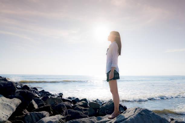女子高生ビーチ - 制服 ストックフォトと画像