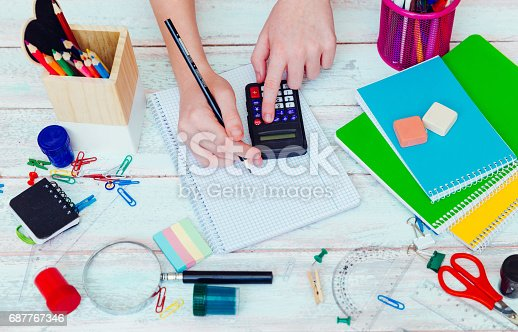 istock schoolgirl on math lesson checking the result on calculator 687767346
