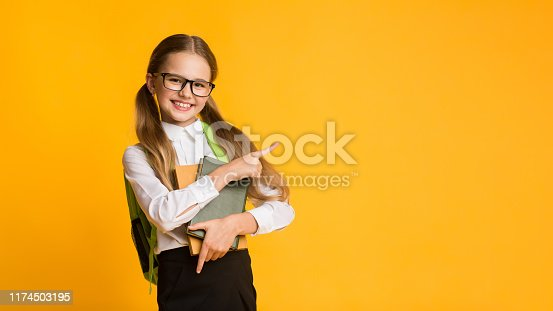 Look There. Cute Schoolgirl Pointing Finger Aside At Empty Space For Text On Yellow Background. Studio Shot, Panorama