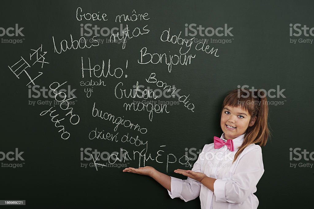 Schoolgirl presenting foreign phrases on blackboard stock photo