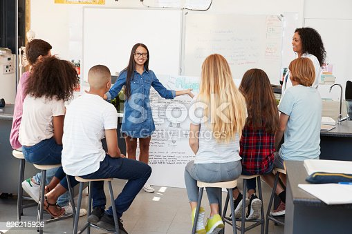 istock Schoolgirl presenting in front of science class, close up 826215926