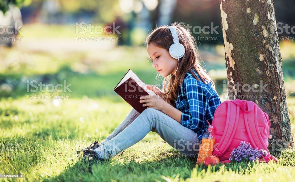 Schoolgirl reading a book. Education, lifestyle concept stock photo