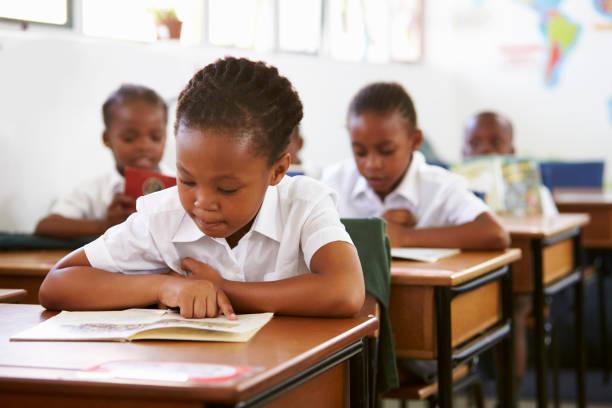 schoolgirl reading at her desk in elementary school lesson - bambine africa foto e immagini stock