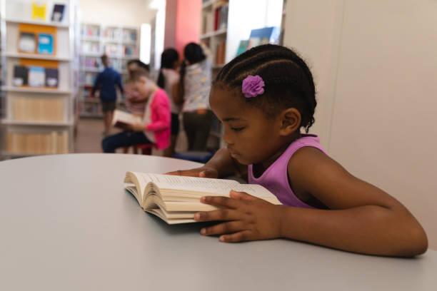 Schulmädchen-Lesebuch am Tisch in der Schulbibliothek – Foto