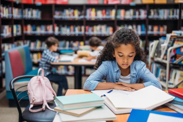 schoolmeisje leesboek in bibliotheek - a little girl reading a book stockfoto's en -beelden