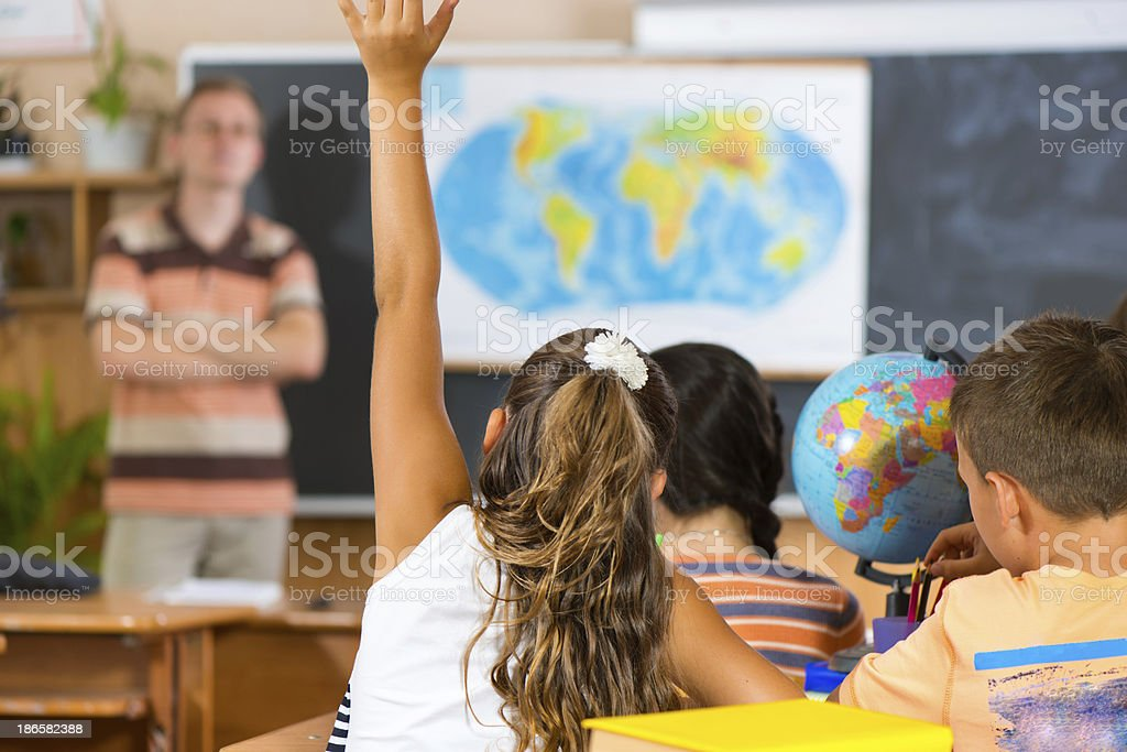 Schoolgirl rising her hand at geography lesson stock photo