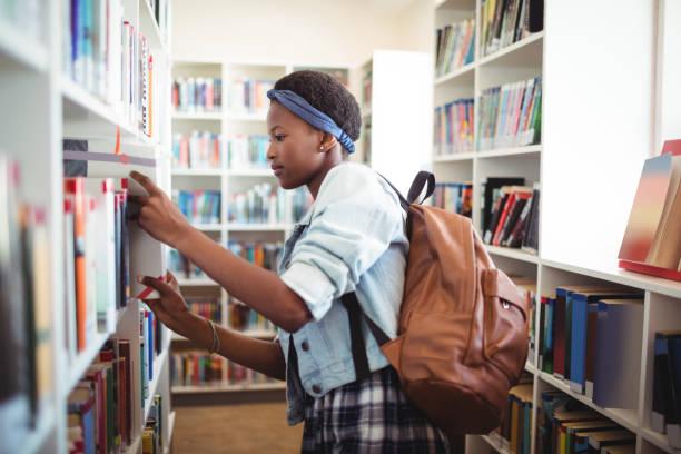 schulmädchen bücherregal in bibliothek buch auswählen - bibliothekschilder stock-fotos und bilder