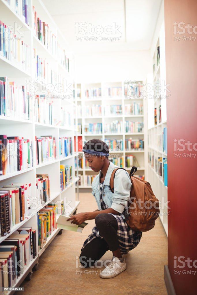 Schoolgirl selecting book from book shelf in library stock photo