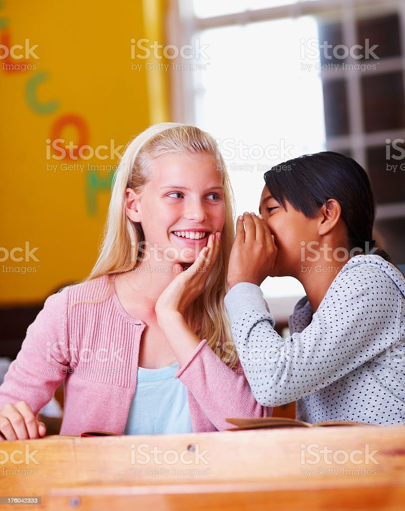 Schoolgirl sharing a secret with her friend royalty-free stock photo