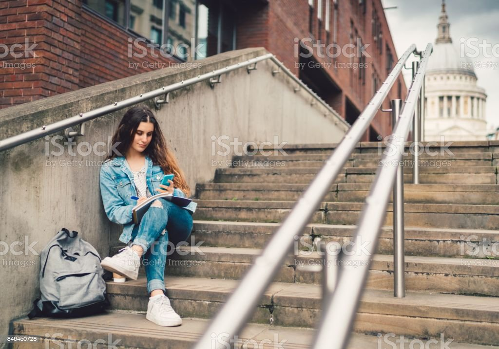 Schoolgirl sitting at the staircase and texting stock photo
