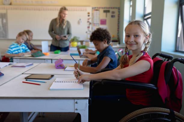 Schoolgirl sitting in a wheelchair in an elementary school classroom stock photo