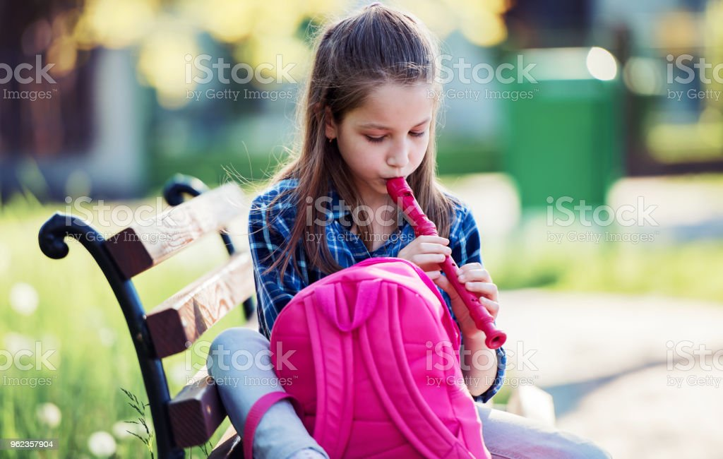 Schoolgirl sitting on the bench in the city park and playing flute. Education, lifestyle concept stock photo