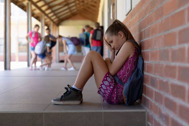 Schoolgirl sitting on the ground against a wall alone in the schoolyard at elementary school stock photo