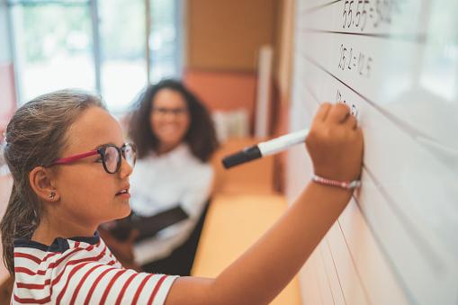 istock Schoolgirl solving maths at white blackboard in class 1069163368