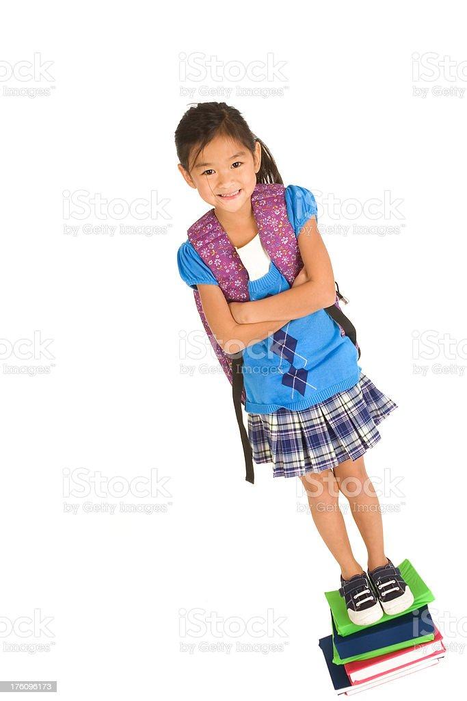 Schoolgirl standing on textbooks royalty-free stock photo