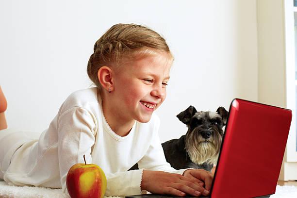 Schoolgirl studies at home on a laptop stock photo