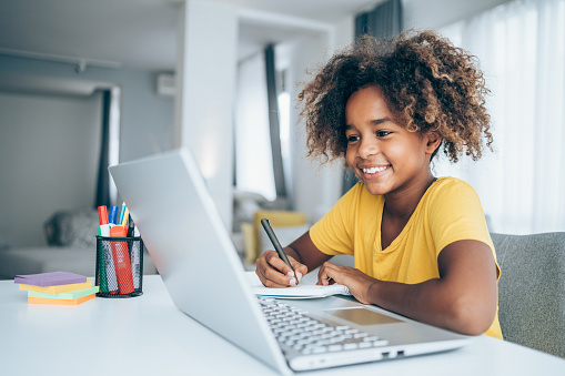 Young student watching lesson online and studying from home. Girl using laptop for online lessons. Homeschooling and distance learning concept.