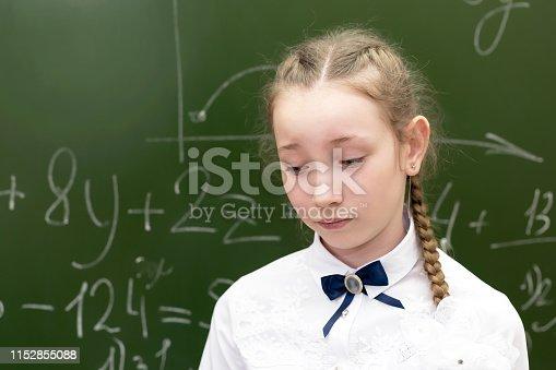 istock Schoolgirl teenager sad at the school blackboard. 1152855088