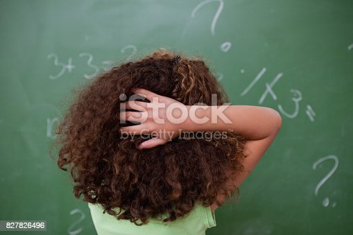 istock Schoolgirl thinking about algebra while scratching the back of her head 827826496