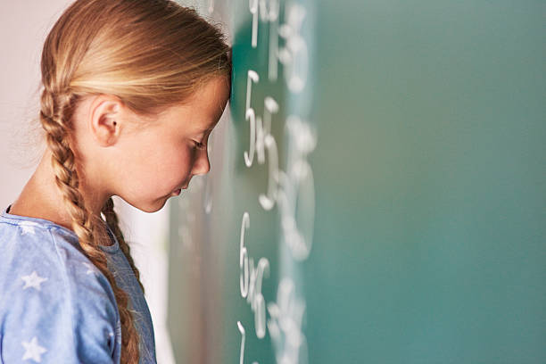 Schoolgirl trying to understand formula ストックフォト