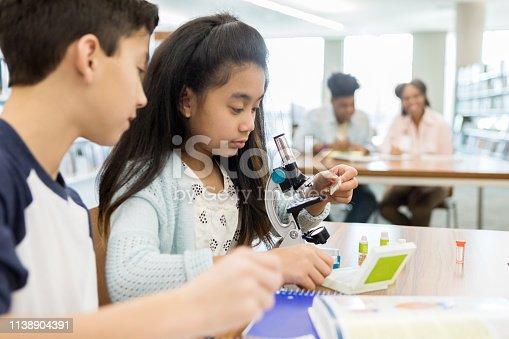 istock Schoolgirl uses microscope during science lab 1138904391
