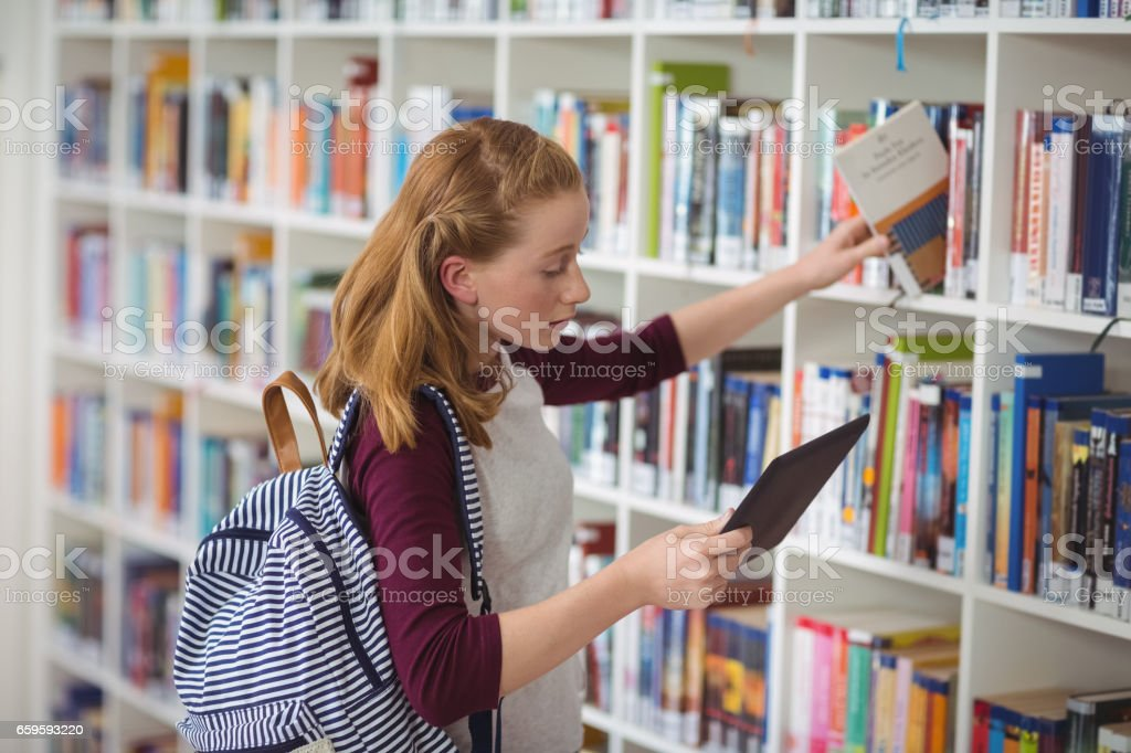 Schoolgirl using digital tablet while selecting book in library stock photo