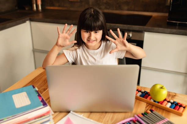 Schoolgirl washed her hands with a sanitizer before starting an online lesson and shows her hands to a teacher stock photo