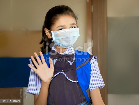 Portrait of happy schoolgirl in uniform with school bag, wearing surgical face mask for protect flu virus and looking at camera. She is standing near door and waving hand in to the camera.
