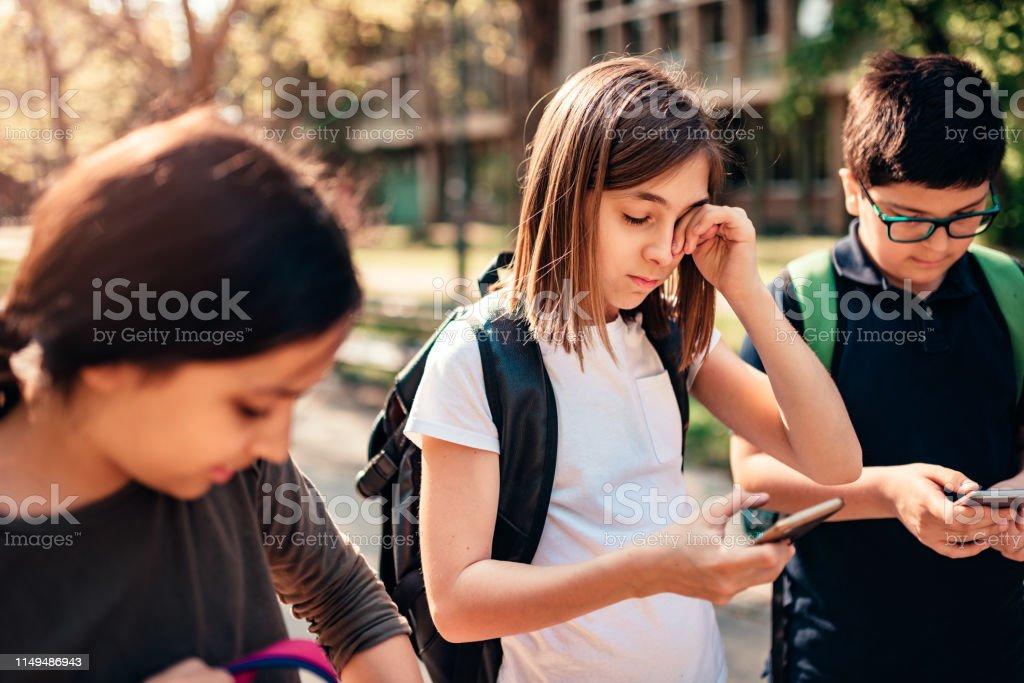Schoolgirl with allergy rubbing eye and using smart phone in...