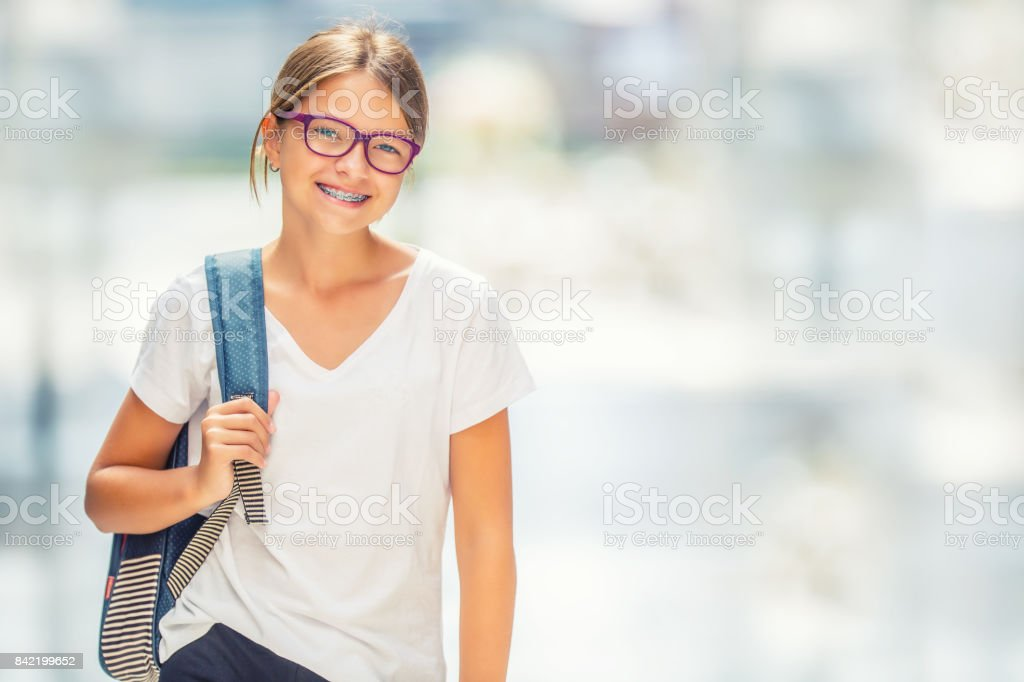 Schoolgirl with bag, backpack. Portrait of modern happy teen school girl with bag backpack. Girl with dental braces and glasses стоковое фото