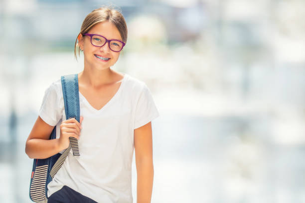 Schoolgirl with bag, backpack. Portrait of modern happy teen school girl with bag backpack. Girl with dental braces and glasses stock photo