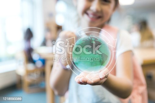 A cute Hispanic elementary schoolgirl smiles cheerfully while holding a digitally enhanced globe in her hand. Focus is on the globe.