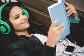 Charming girl enjoying the music from smartphone and reading a book