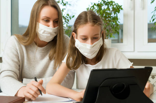 Schoolgirl with her mother at distance learning. Home schooling concept. stock photo