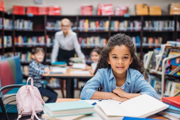 schoolgirl with pile of books at library - scolara foto e immagini stock