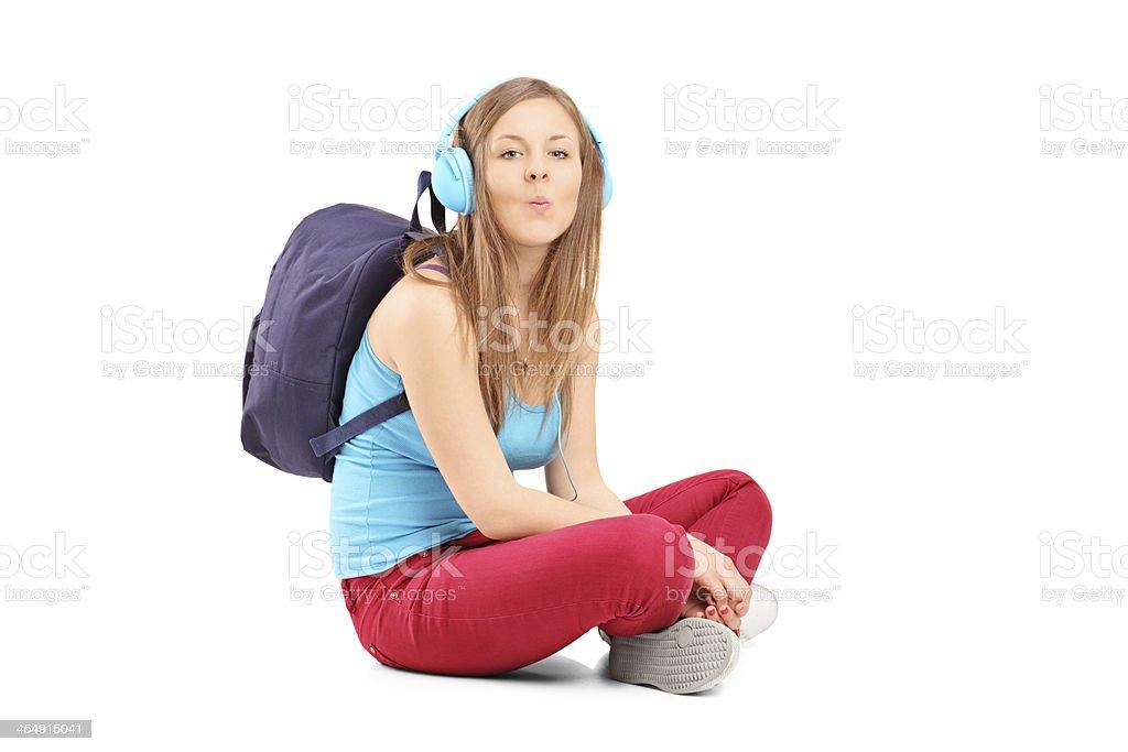 Schoolgirl with speakerphones sitting and giving kisses stock photo