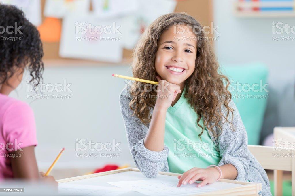 Schoolgirl working on math worksheet stock photo