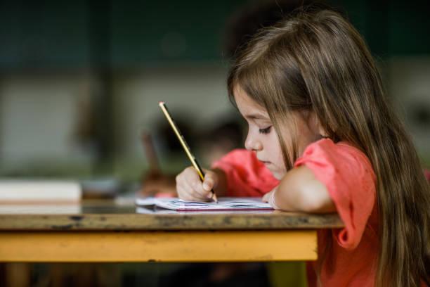 schulmädchen schreiben ein diktat während einer klasse in der grundschule. - grundschule stock-fotos und bilder